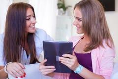 Deux amis gais ayant l'amusement et regardant le PC mobile de comprimé Image stock