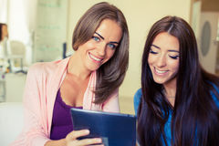Deux amis gais ayant l'amusement et regardant le PC mobile de comprimé Photos stock