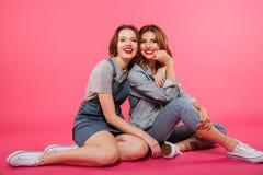 Deux amis gais de femmes s'asseyant sur le plancher Photographie stock