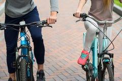 Deux amis gais se reposant avec des bicyclettes Photo stock