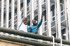 Deux amis grêlent des autres personnes dans la rue Image libre de droits