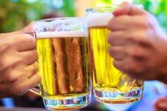 Deux amis grillant avec des verres de bière Photo libre de droits