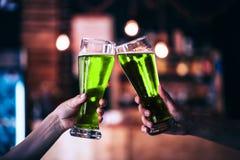 Deux amis grillant avec des verres de bière verte Images stock