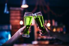 Deux amis grillant avec des verres de bière verte Image stock