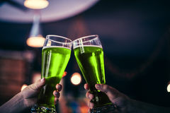 Deux amis grillant avec des verres de bière verte Photos stock