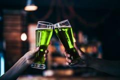 Deux amis grillant avec des verres de bière verte Photographie stock libre de droits