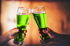 Deux amis grillant avec des verres de bière verte Images libres de droits