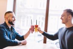 Deux amis heureux avec les smoothies colorés Image libre de droits