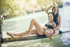 Deux amis heureux détendant à l'oscillation à la plage tropicale d'océan Photo stock