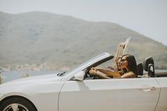 Deux amis heureux dans la conduite blanche de cabriolet partout Photographie stock libre de droits