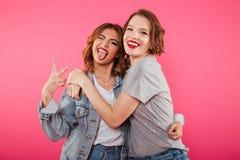 Deux amis heureux de femmes étreignant montrant le geste de paix Image libre de droits
