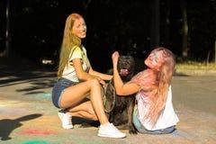 Deux amis heureux de femmes jouant avec le grand chien au festival de Holi Image stock