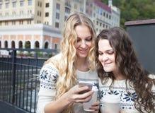 Deux amis heureux de femmes partageant le media social à une OU futée de téléphone Photo libre de droits