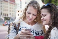Deux amis heureux de femmes partageant le media social à une OU futée de téléphone Photographie stock