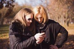 Deux amis heureux de femmes partageant le media social à une OU futée de téléphone Image libre de droits