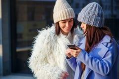 Deux amis heureux de femmes partageant le media social dans un téléphone intelligent dehors Photo stock