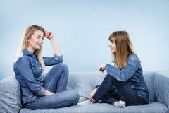 Deux amis heureux de femmes portant parler d'équipement de jeans Image libre de droits