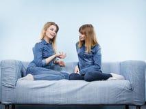 Deux amis heureux de femmes portant parler d'équipement de jeans Images stock