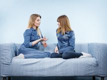 Deux amis heureux de femmes portant parler d'équipement de jeans Photo libre de droits