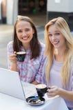 Deux amis heureux de femmes regardant l'appareil-photo avec la tasse de café Images stock