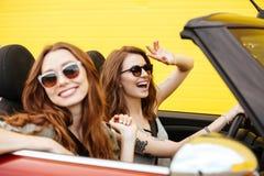 Deux amis heureux de femmes s'asseyant dans la voiture au-dessus du mur jaune Photographie stock libre de droits