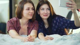 Deux amis heureux de femmes se situant dans le lit et faisant le selfie dans le matin et ont l'amusement sur le lit Images libres de droits