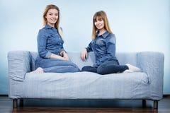 Deux amis heureux de femmes utilisant l'équipement de jeans Images stock
