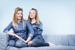 Deux amis heureux de femmes utilisant l'équipement de jeans Photographie stock