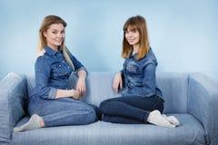 Deux amis heureux de femmes utilisant l'équipement de jeans Images libres de droits