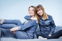 Deux amis heureux de femmes utilisant l'équipement de jeans Image libre de droits