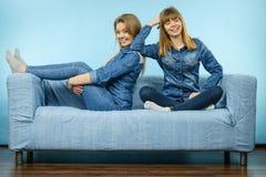 Deux amis heureux de femmes utilisant l'équipement de jeans Photos libres de droits