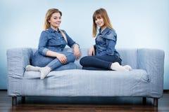 Deux amis heureux de femmes utilisant l'équipement de jeans Photo stock