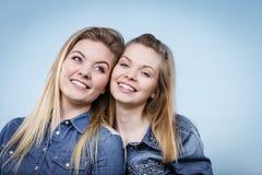 Deux amis heureux de femmes utilisant l'équipement de jeans poitning Photo stock