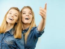 Deux amis heureux de femmes utilisant l'équipement de jeans poitning Photographie stock libre de droits