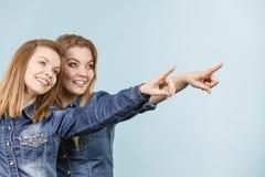 Deux amis heureux de femmes utilisant l'équipement de jeans poitning Image libre de droits
