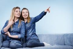 Deux amis heureux de femmes utilisant l'équipement de jeans poitning Photos stock