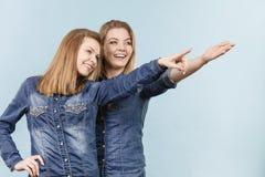 Deux amis heureux de femmes utilisant l'équipement de jeans poitning Images stock