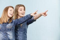 Deux amis heureux de femmes utilisant l'équipement de jeans poitning Photo libre de droits