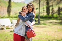 Deux amis heureux de jeunes femmes étreignant en parc urbain Photographie stock