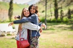 Deux amis heureux de jeunes femmes étreignant en parc urbain Images stock