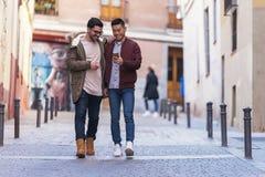Deux amis heureux employant le mobile dans la rue Photos libres de droits