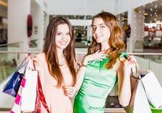 Deux amis heureux faisant des emplettes dans le mail Images stock