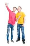 Deux amis heureux faisant des selfies sur le fond d'isolement Image libre de droits