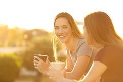 Deux amis heureux parlant dans un balcon au coucher du soleil Photographie stock libre de droits