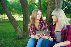 Deux amis heureux recherchant le contenu de médias en ligne dans un ordinateur portable se reposant sur l'herbe en parc image stock