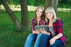 Deux amis heureux recherchant le contenu de médias en ligne dans un ordinateur portable se reposant sur l'herbe en parc image libre de droits