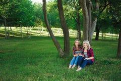 Deux amis heureux recherchant le contenu de médias en ligne dans un ordinateur portable se reposant sur l'herbe en parc photos stock