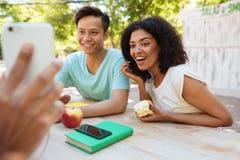Deux amis heureux regardant le smartphone Image stock