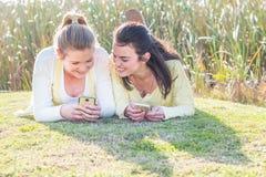 Deux amis heureux s'étendant sur l'herbe en parc agissant l'un sur l'autre Image stock