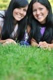 Deux amis heureux se situant à l'extérieur dans l'herbe Image libre de droits